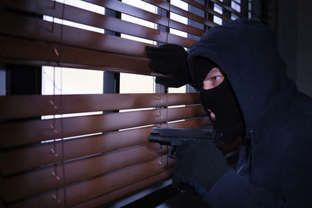 Masked man with gun spying through window blinds indoors. Criminal offence Stock Photo