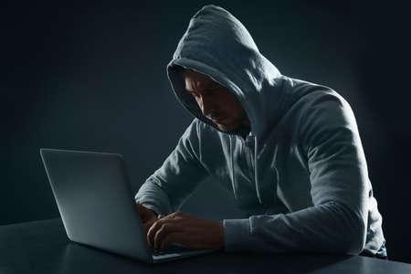 Man using laptop at table on dark background. Criminal activity