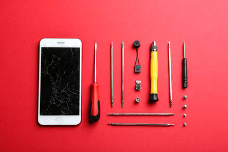 Flat lay composition with broken mobile phone and repair tools on color background