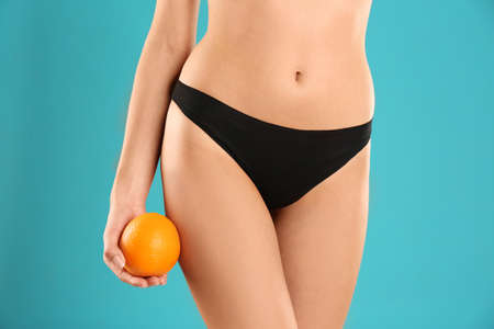 Closeup view of slim woman in underwear with orange on color background. Cellulite problem concept