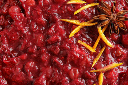 Tasty cranberry sauce with citrus zest and anise as background, top view