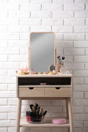 Dressing table with different makeup products and accessories in room interior