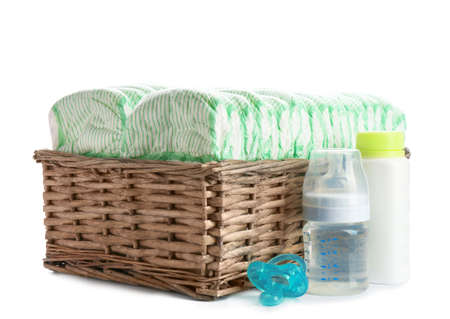 Basket with diapers and baby accessories on white background Banque d'images