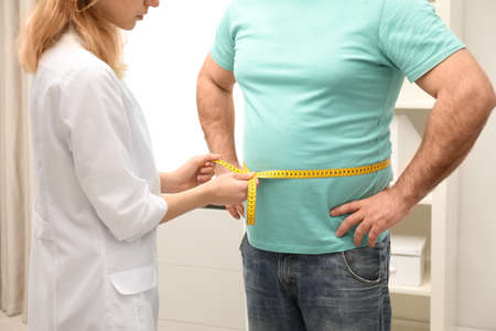 Doctor measuring overweight man's waist in hospital, closeup