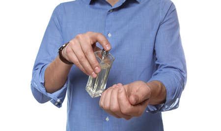 Man applying perfume on wrist against white background, closeup