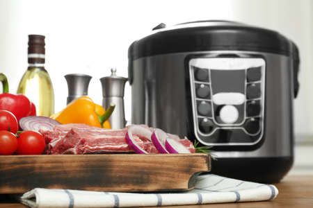 Modern multi cooker and products on wooden table in kitchen