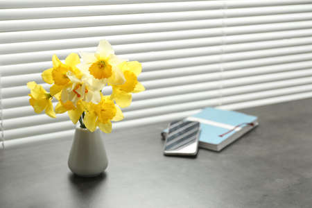 Beautiful narcissus flowers in vase near window with blinds. Space for text