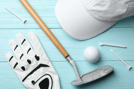 Flat lay composition with golf accessories on blue wooden background
