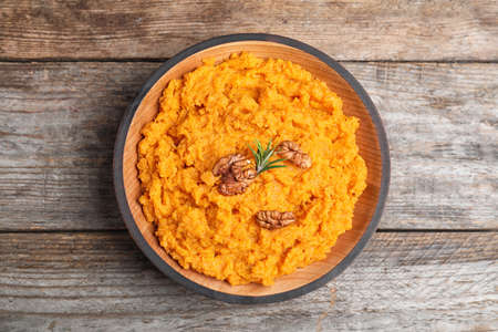 Bowl with mashed sweet potatoes on wooden table, top view