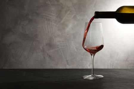 Pouring red wine from bottle into glass on table. Space for text Archivio Fotografico - 123307905