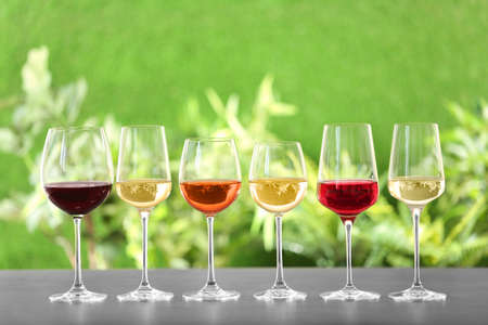 Row of glasses with different wines on grey table against blurred background