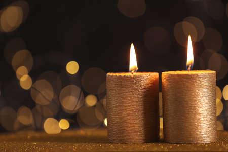 Velas de oro encendidas en la mesa contra luces borrosas. Espacio para texto Foto de archivo