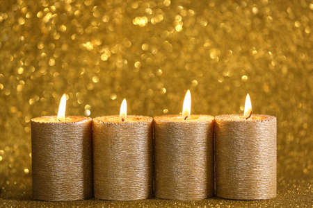 Stylish burning candles on gold shining background, space for text