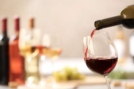 Versare il vino rosso dalla bottiglia in vetro su sfondo sfocato. Spazio per il testo