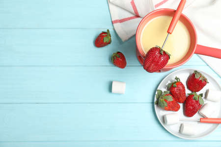 Chocolate fondue with strawberries and marshmallow on wooden table, flat lay. Space for text Banque d'images