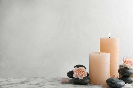 Composition of burning candles, spa stones and flowers on table. Space for text 스톡 콘텐츠