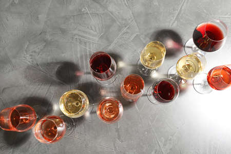 Different glasses with wine on grey background, flat lay