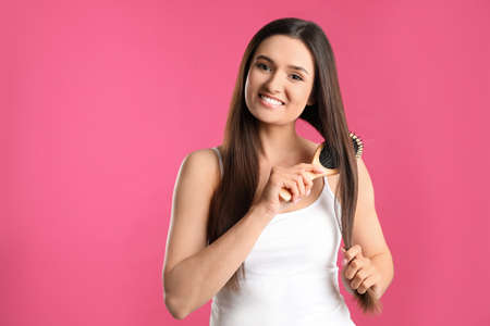 Beautiful smiling young woman with hair brush on color background