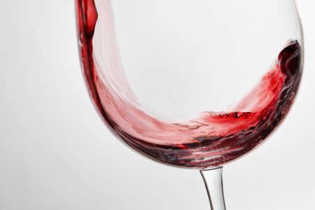 Verter el vino tinto en vaso sobre fondo claro, primer plano Foto de archivo