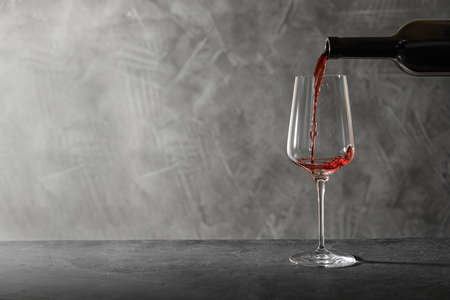Pouring red wine from bottle into glass on table. Space for text