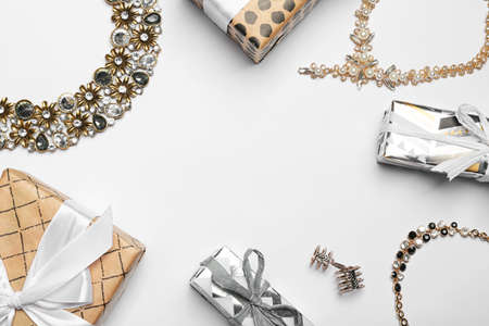 Beautiful jewelry and gift boxes on light background, flat lay. Space for text