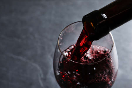 Pouring red wine from bottle into glass on grey background, closeup. Space for text