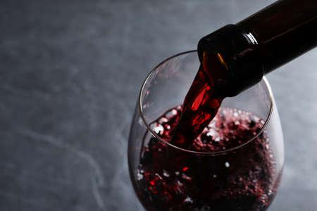 Verter el vino tinto de la botella en vidrio sobre fondo gris, primer plano. Espacio para texto Foto de archivo
