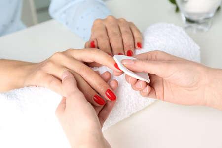 Manicurista quitando el esmalte de las uñas del cliente en el salón, primer plano