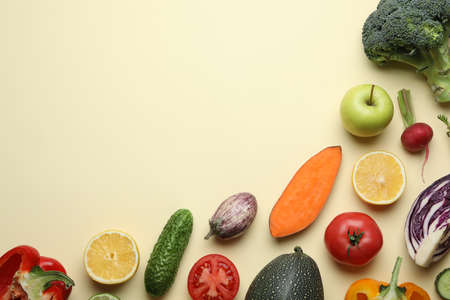 Flat lay composition with fresh ripe vegetables and fruits on color background. Space for text