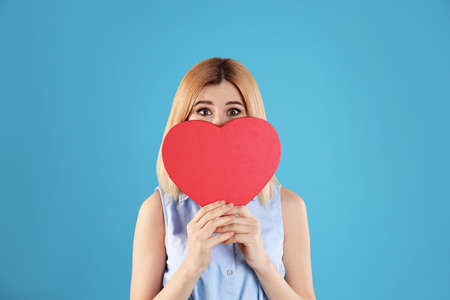 Beautiful woman with heart shaped box on color background Stock Photo