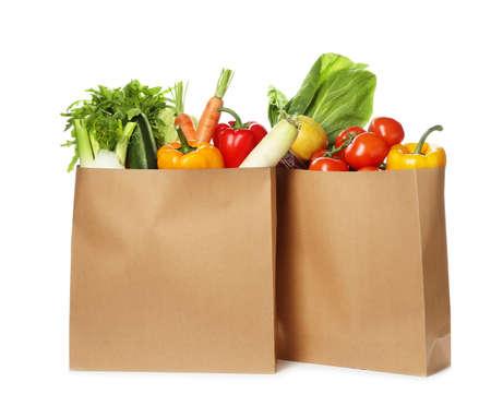 Bolsas de papel con verduras frescas sobre fondo blanco. Foto de archivo