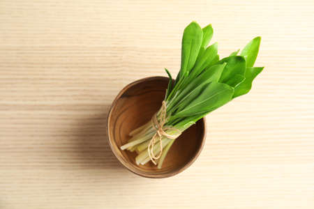 Bowl with bunch of wild garlic or ramson on wooden table, top view