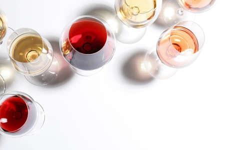 Verschiedene Gläser mit Wein auf weißem Hintergrund, Ansicht von oben