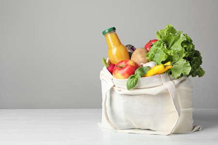Bolsa de tela con verduras y una botella de jugo en la mesa contra un fondo gris. Espacio para texto Foto de archivo