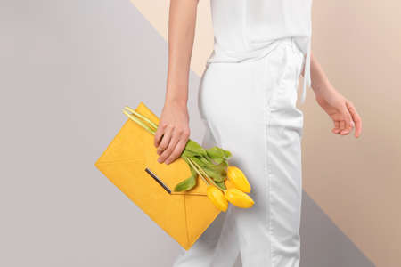 Stylish woman with clutch and spring flowers against color background, closeup Banque d'images