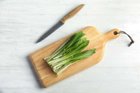 Board with wild garlic or ramson and knife on white wooden table, flat lay