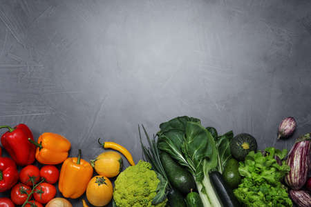 Flat lay composition with fresh vegetables and space for text on grey background