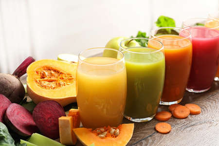Glasses with different juices and fresh ingredients on wooden table