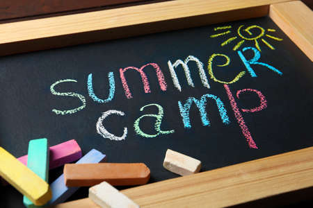 Small blackboard with text SUMMER CAMP, drawing and chalk sticks on wooden background, closeup