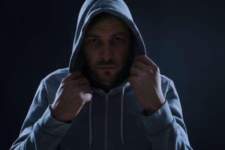 Hombre misterioso con capucha sobre fondo oscuro. Criminal peligroso Foto de archivo