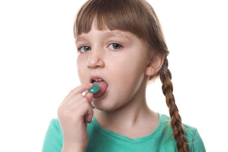 Little child taking pill on white background. Danger of medicament intoxication Stock Photo
