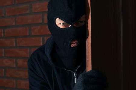 Man in mask spying behind door indoors. Criminal activity