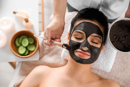 Cosmetologist applying black mask onto woman's face in spa salon, top view