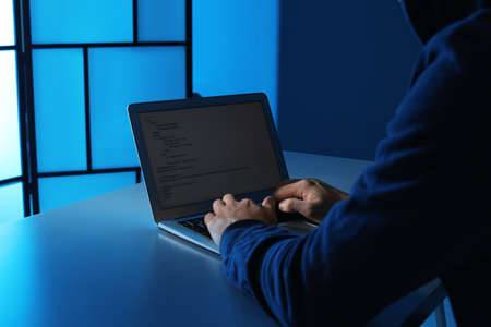 Man using laptop at table in dark room, closeup. Criminal offence Stock Photo