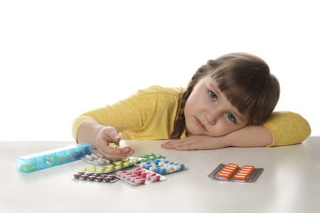 Little child with many different pills on white background. Danger of medicament intoxication