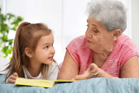 Cute girl and her grandmother reading book on bed at home Stock Photo