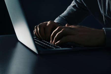 Man using laptop at table on dark background, closeup. Criminal activity