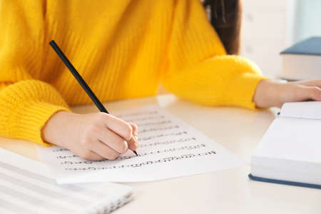 Child writing music notes at table, closeup