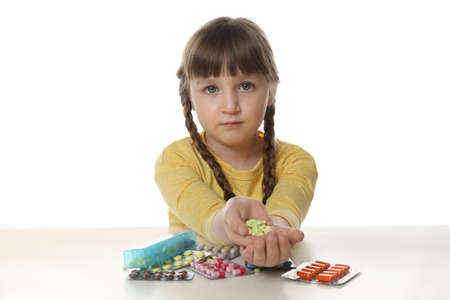 Little child with many different pills on white background. Danger of medicament intoxication Stock Photo