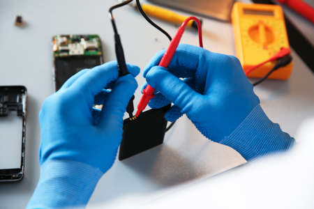 Technician checking mobile phone battery at table in repair shop, closeup Imagens